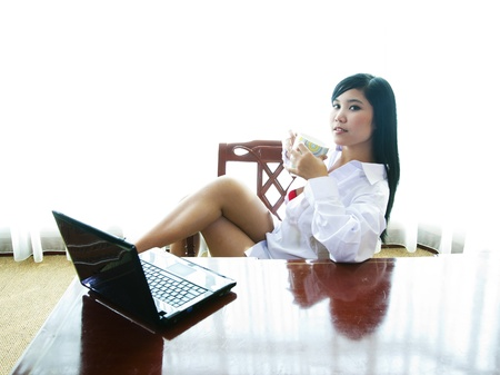 teacup: Sexy asian businesswoman with laptop and a mug of coffee