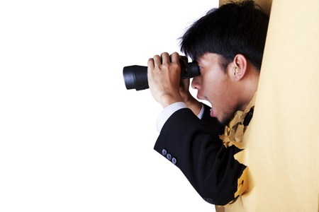 Shocked businessman breaking through a paper wall looking through binoculars photo