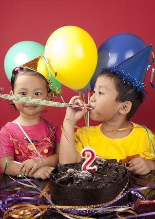 bugle: Asian sibling celebrating birthday Stock Photo