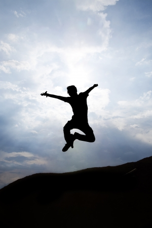 Silhouette of jumping happy man photo
