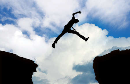 flying man: Dangerous silhouette of man jumping cliff Stock Photo