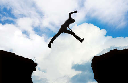 leap: Silhouette of young man jumping over cliff Stock Photo
