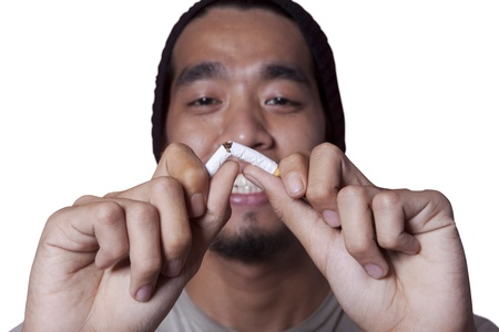 quit smoking: Asian man breaks a cigarette to quit smoking