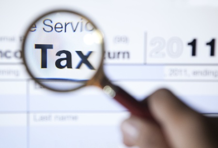 tax: Magnifying glass over the word tax on form 1040