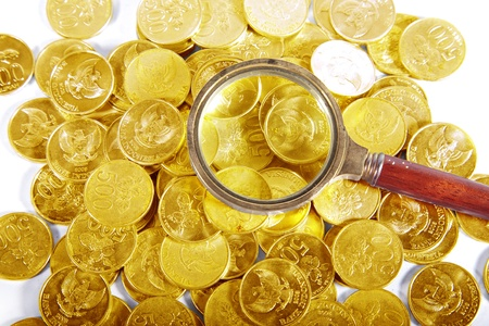 pile of coins: Pile of golden coins with magnifying Stock Photo