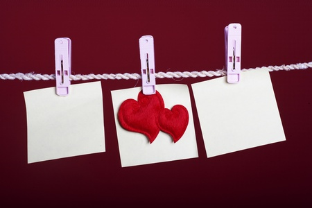 Valentine Concept: three blank notes hanging with heart hanging in the middle. photo
