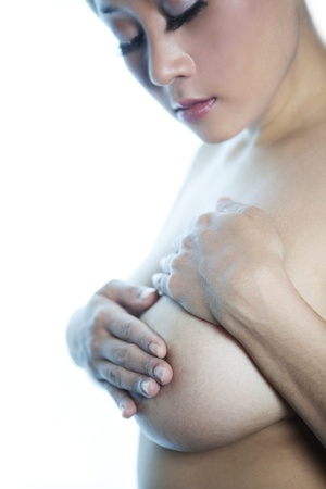 Asian woman examine her breast shot over white background photo