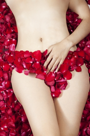 Hips of slim tanned woman lying on red roses petals photo