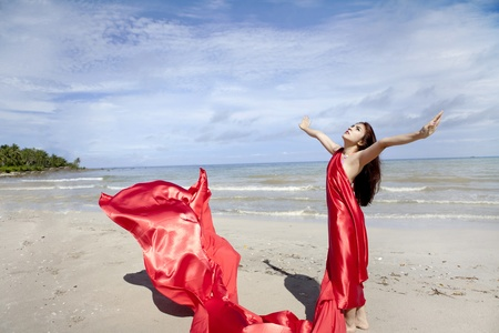 beach wrap: Young woman in red scarf stretch hand on the beach