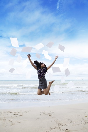 Happy young businesswoman jumps with paperwork on the beach photo