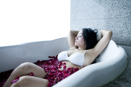 sexy asian woman: Sexy Asian woman reaxing in bathtub with rose petals Stock Photo