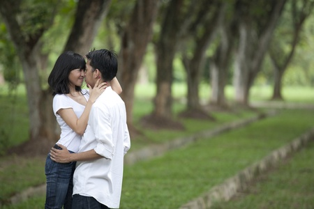 Asian young couple hugging in the park photo