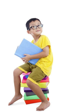 comprehension: Smart Asian kid with glasses sitting on stack of books isolated on white