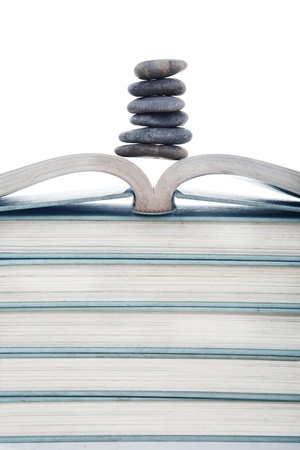 Corporate concept - A stack of stones on pile of corporate books photo
