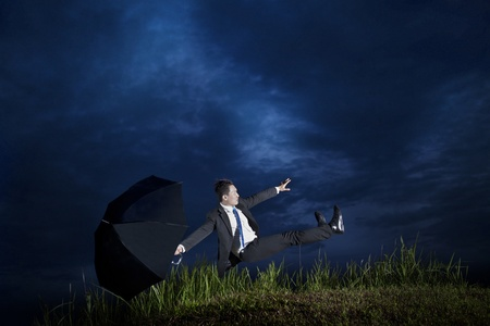 Asian Businessman with umbrella falling down photo