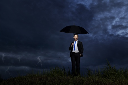 Asian businessman with umbrella standing on a cloudy day with thunderstorm photo
