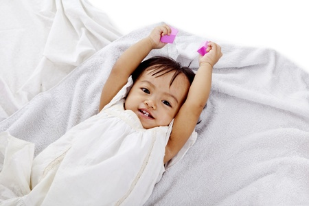 Cute girl smiling on bath towel while holding blocks photo