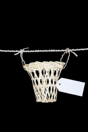 An empty basket with name tag over black background photo