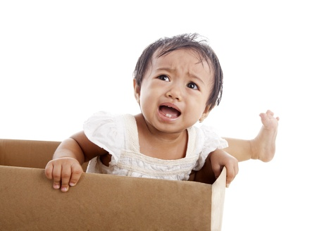 A toddler frustrated that she can not out of a box photo