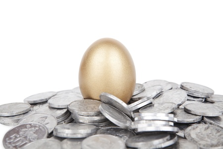 Golden egg with coins on white background photo