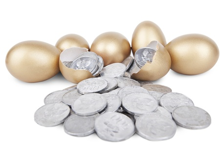 priceless: Golden eggs with coins on white background Stock Photo