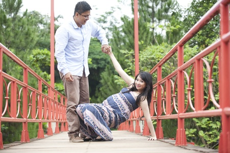 Husband helps his pregnant wife to stand photo