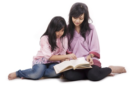 Mother spending the time together with her daughter reading a book