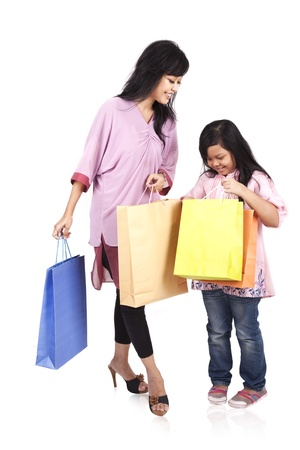 Happy mother and daughter holding shopping bags isolated on white photo