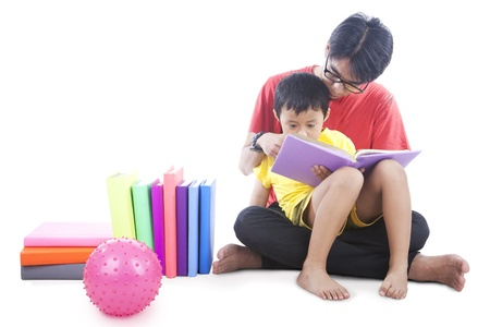 Little boy reading a book with dad photo