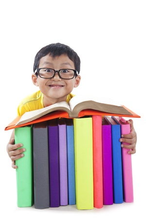 Smart boy smiling with pile of textbooks photo