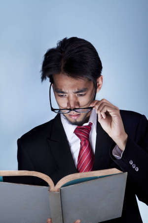 Business man reading a book over a blue background photo