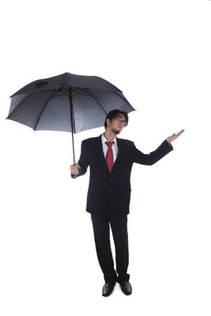 Businessman holding umbrella with arm outstretched Stock Photo - 12652213