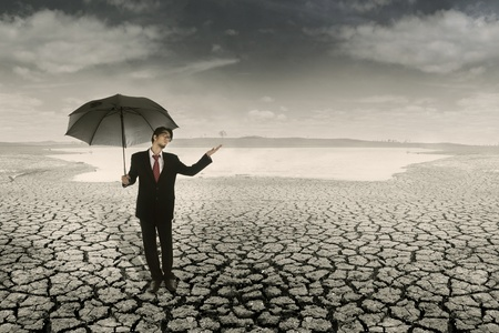 Businessman with umbrella standing on cracked earth waiting for the rain photo