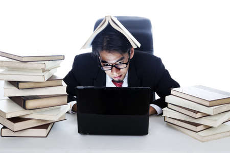 Businessman working on laptop with a book on his head photo