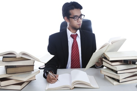 Busy businessman makes note from textbooks photo