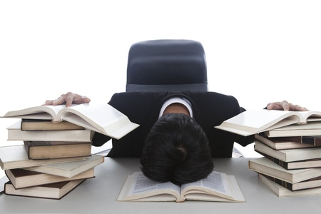 A businessman exhausted to work sleep in his office with stacks of books photo
