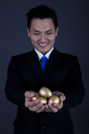 accrue: Businessman holding golden eggs - investment concept