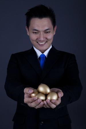 accrue: Businessman holding golden eggs - investment concept