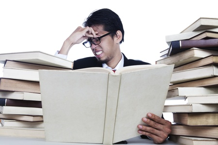 A businessman having headache after read books photo