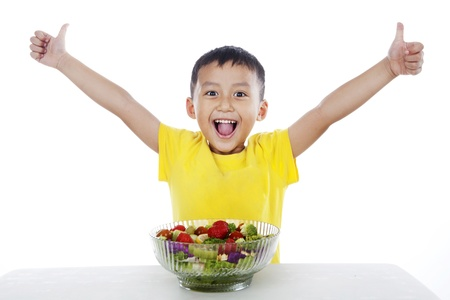 kids eating: Young boy with healthy salad, shot in studio isolated on white background