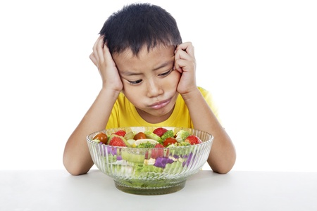 bored face: Lazy child to eat salad, shot in studio isolated on white background  Stock Photo