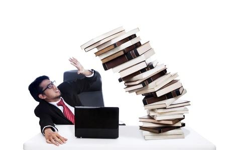 accidente trabajo: Hombre de negocios asustado con los libros de la pila, que a punto de derrumbarse. Filmado en el estudio aislado en blanco