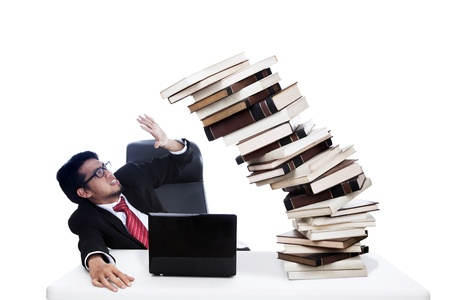 accident at work: Scared businessman with stack books which about to collapse. Shot in studio isolated on white
