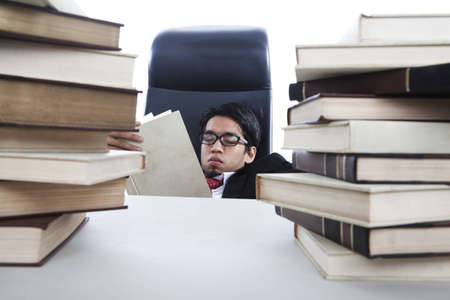 A businessman sleeps in office as he is overwhelmed to read books photo