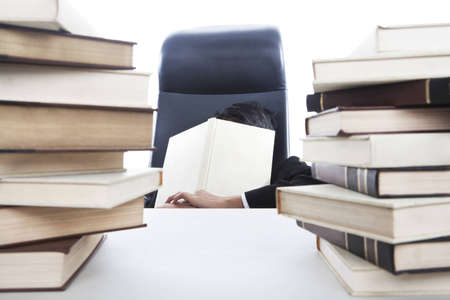 pile of paper: Overworked businessman sleeping in office while holding a book