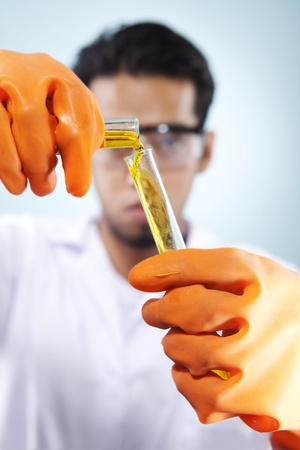 A scientist pouring the liquid chemical to his research in the laboratory research photo