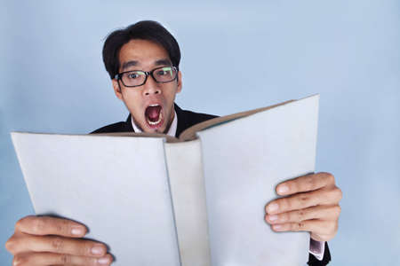 Shocked businessman reading a book photo