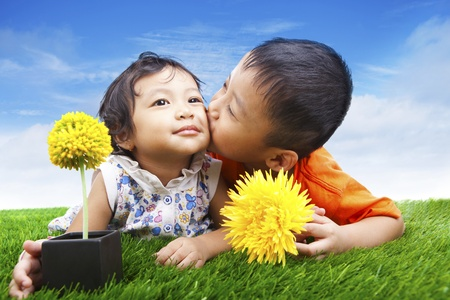 Attractive boy kissing his sister on the green grass with flowers photo