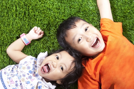 Closeup of happy young children lying on the green grass photo