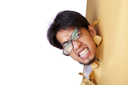 Mad businessman wearing glasses breaking through a paper wall photo